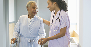 Photo of nurse assisting elderly female patient
