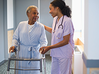 A nurse assists an older patient using a walker