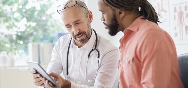 Male doctor looking at IPad with male patient