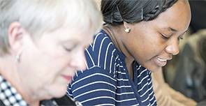 Two women looking down and reading  a patient advisor report