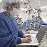 Nurse in full scrubs typing on a computer as doctors perform surgery in the background