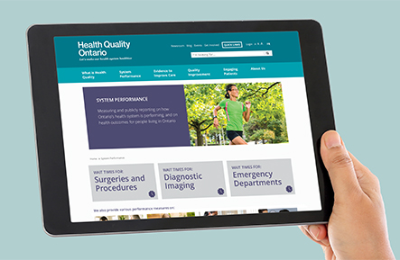 Hand holding tablet with Health Quality Ontario's wait times webpage displayed on it